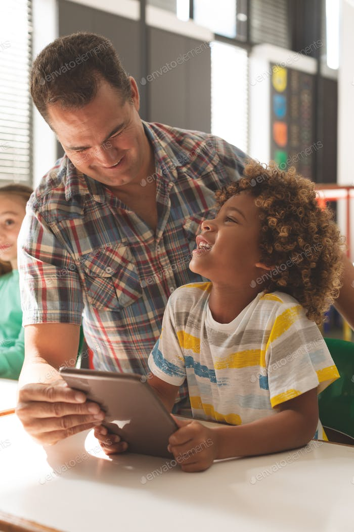Teacher interacting with school boy over digital tablet in classroom at school
