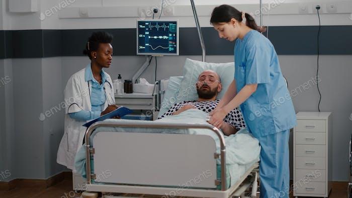 Sick man sitting in bed with oxygen tube explaining disease symptom
