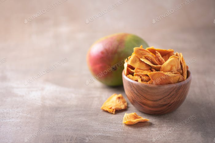 Dried mango in wooden bowl and fresh mango fruit on wood textured background. Copy space. Superfood