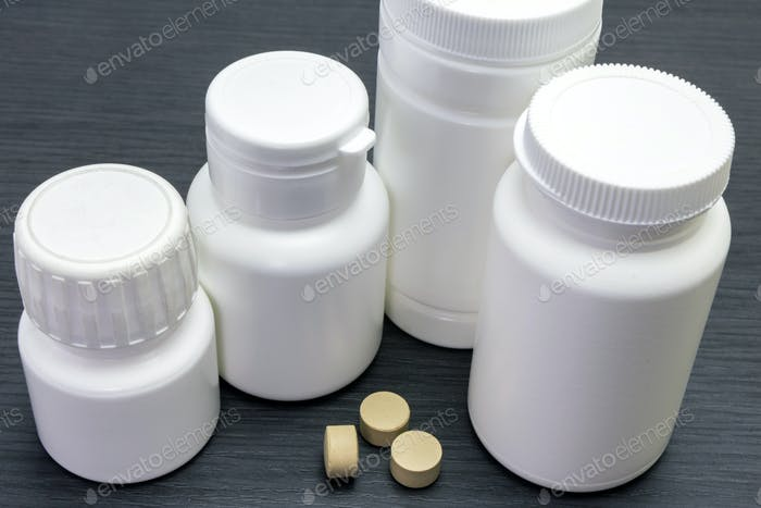 white boats of pills of different sizes, conceptual image