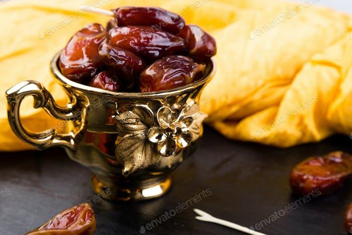Dry fruit dates in golden cup near slate black heart.