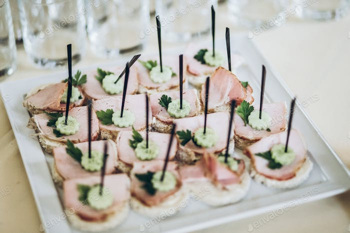 Delicious appetizers canape with ham and cucumber on plate