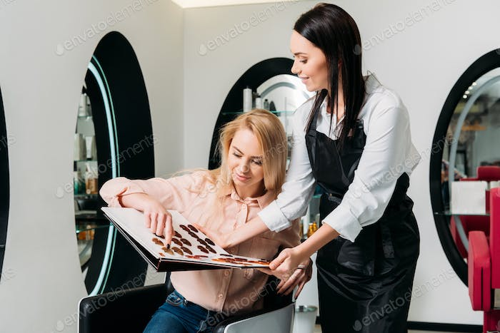 customer choosing color for dyeing hair at salon