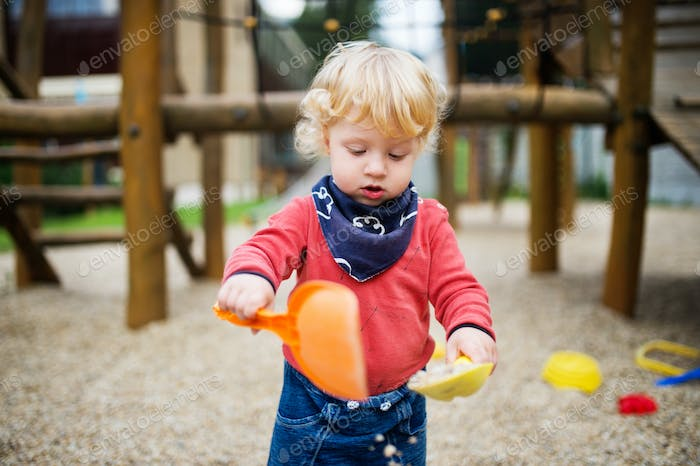 Toddler boy playing in the playground, summer day.