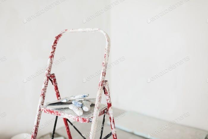 Nahaufnahme Leiter mit Kitt Messer über weißem Hintergrund isoliert