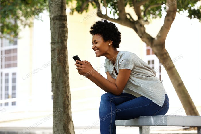 Cheerful young woman sitting on a bench reading text message