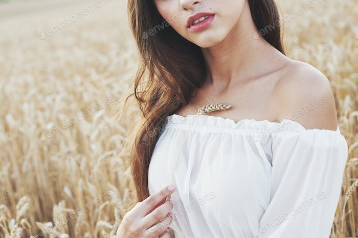 Young sensitive girl in white dress posing in a field of golden wheat