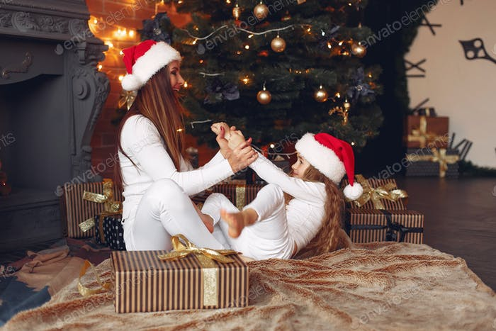 Mother with cute daughter at home near fireplace