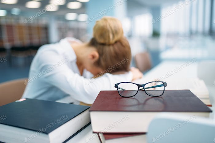 Female person sleeping at the table in library