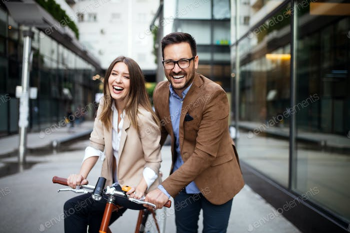 Happy young couple going for a bike ride . Young couple having fun in the city