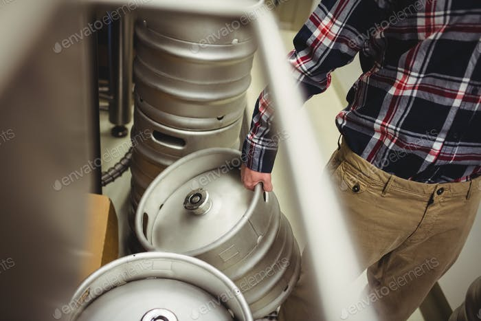 Midsection of manufacturer holding kegs