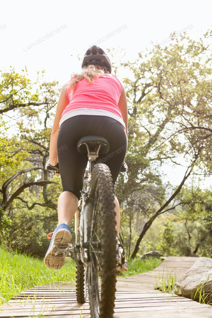 Rear view of blonde athlete mountain biking in the nature