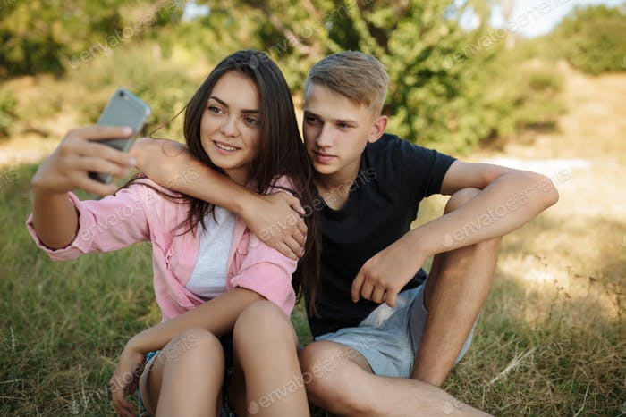 Young pretty couple sitting on lawn in park and making selfie together