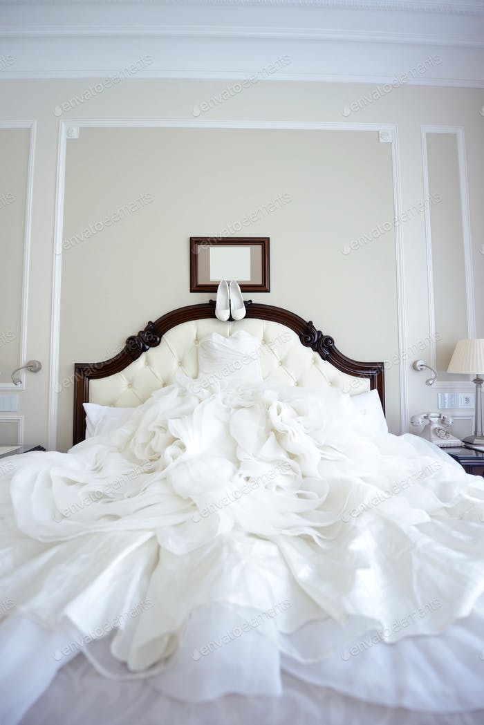 Beautiful white wedding dress and shoes for bride indoors