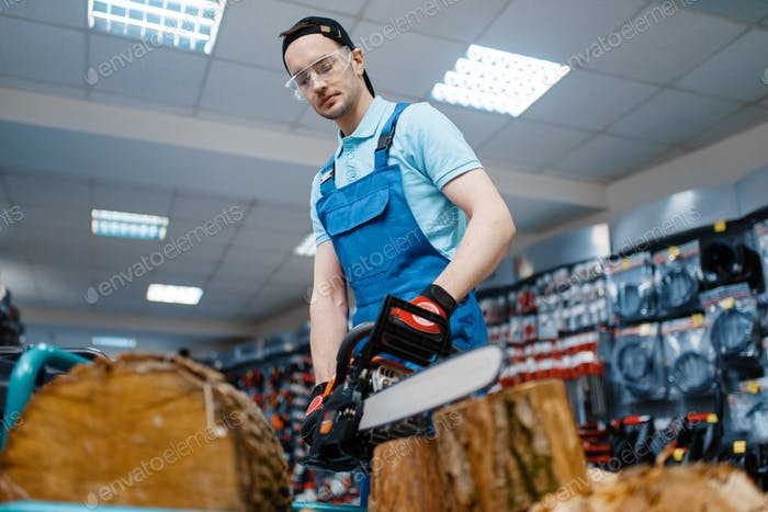 Worker in uniform testing chainsaw in tool store