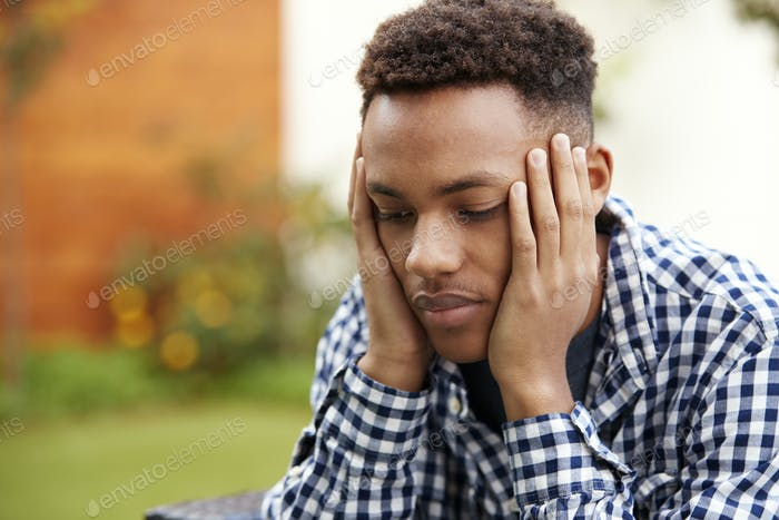 Depressed young black man with head in hands, close up, head and shoulders