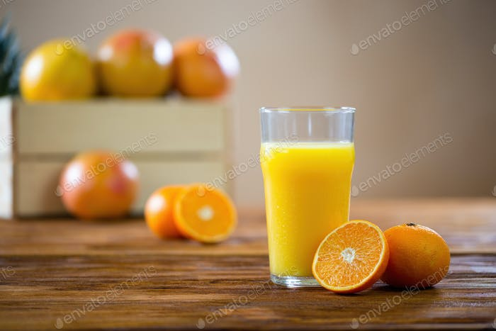 Orange cut in half lying on a wooden table next to glass of squeezed juice