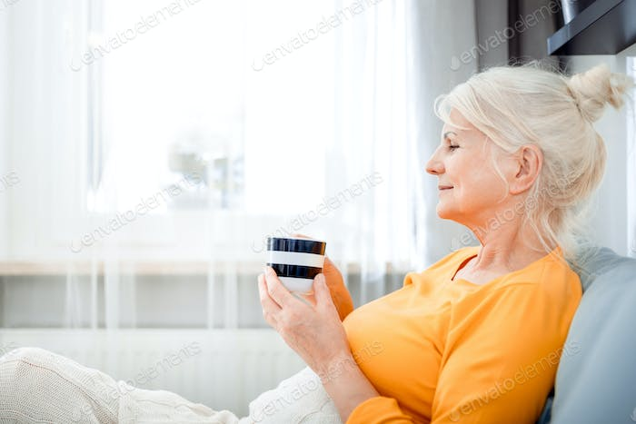 Senior woman at home relaxing on sofa with blanket holding cup of coffee