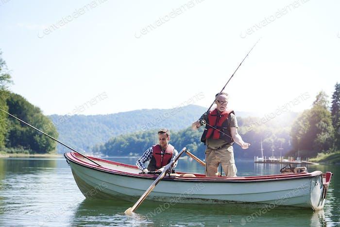 Senior man with son fishing in lake