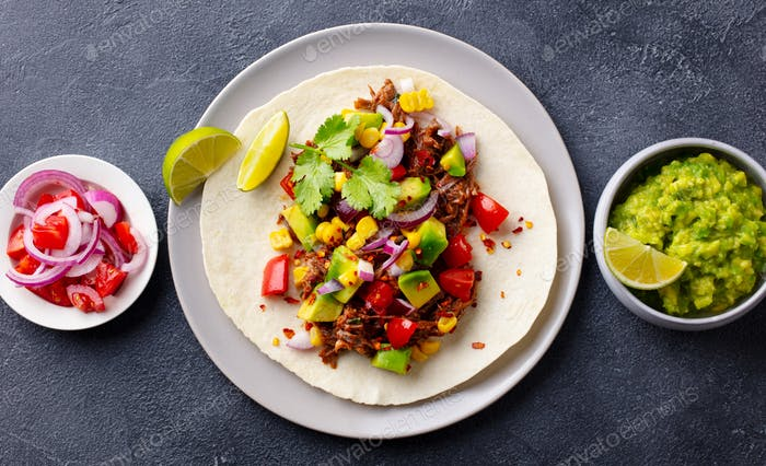 Taco with meat and vegetables. Dark background. Close up. Top view.