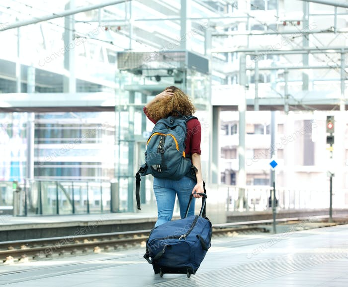 Young woman walking with luggage