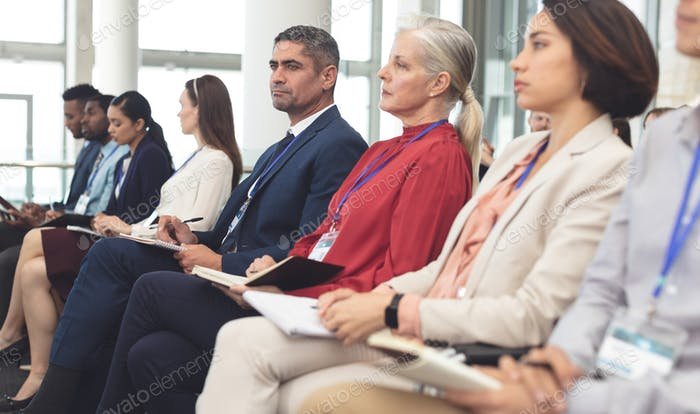 Diverse business people looking serious while attending a business seminar in office building