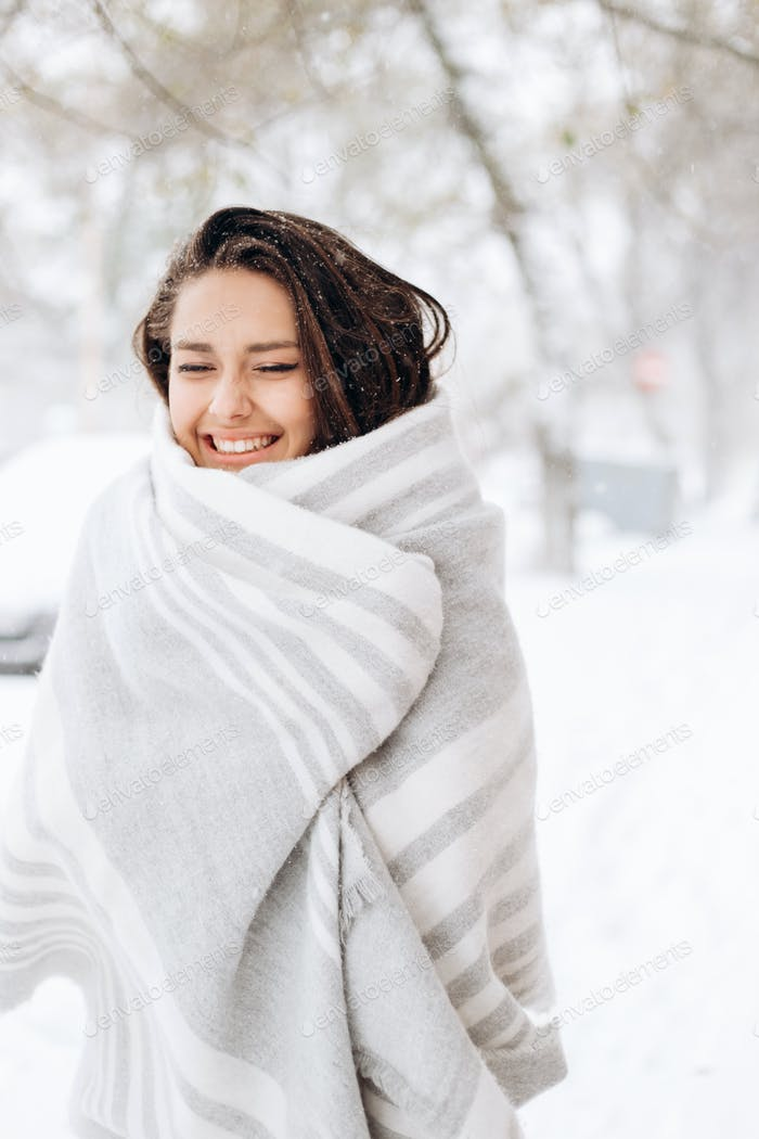 Smiling dark-haired girl wrapped in a gray scarf is standing in a snowy street on a winter day