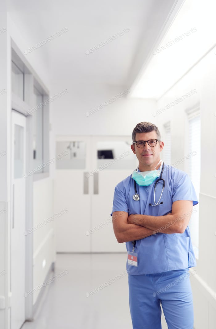 Portrait Of Mature Male Doctor Wearing Scrubs Standing In Hospital Corridor