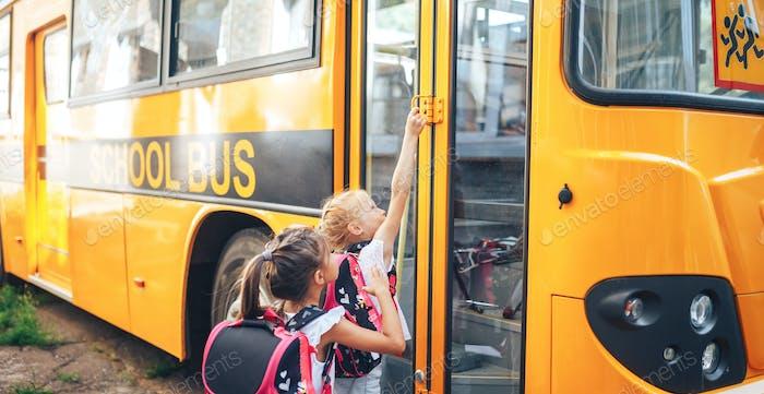 Schoolgirls with backpacks enter the school bus, back to school