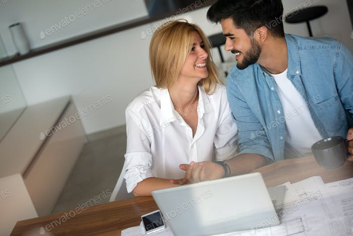 Portrait of a cheerful young couple calculating their bills