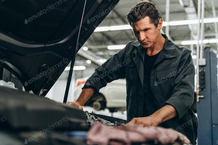 Expertise car mechanic in auto repair service. Caucasian man working attentively