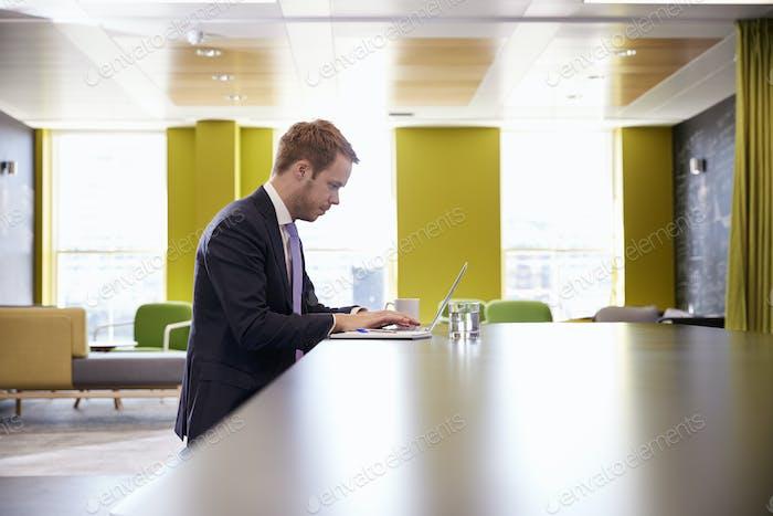 Junge Geschäftsmann arbeitet an einem Laptop im Büro Meeting-Bereich