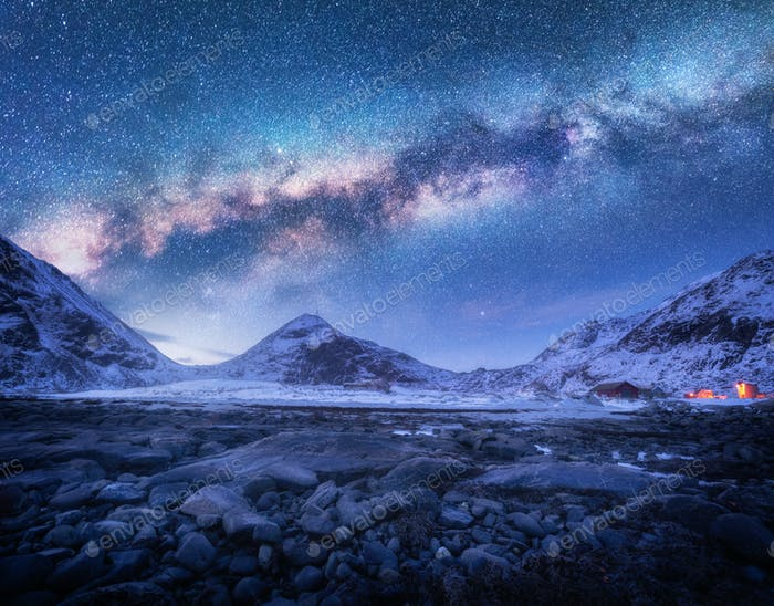 Milky Way above snow covered mountains and stones beach in winter