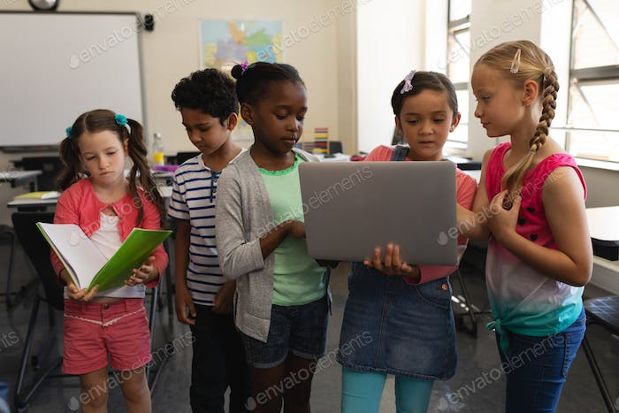 Group of school kids studying together in classroom of elementary school