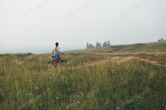 young woman going with bicycle on countryside road in hills