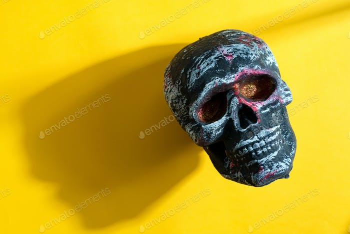 Human skull on a yellow background with shadow.