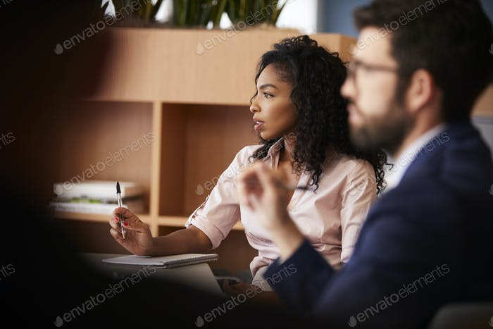 Businesswoman Making Notes Sitting At Table Meeting With Colleagues In Modern Office