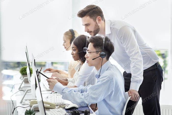 El administrador de servicio al cliente ayuda a su supervisor a ejecutar la solicitud del cliente en el centro de llamadas