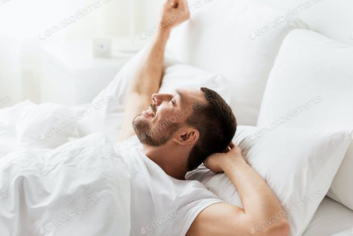 man lying in bed at home