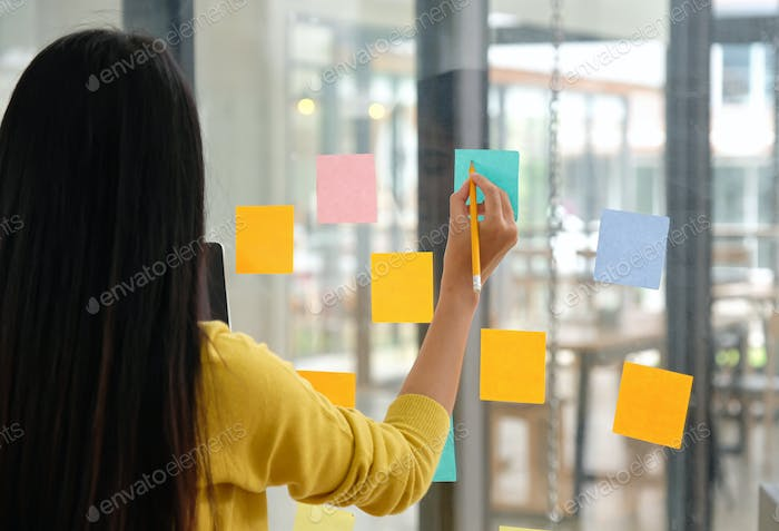 Female staff use a pen to write a papernote on the glass to plan their work.