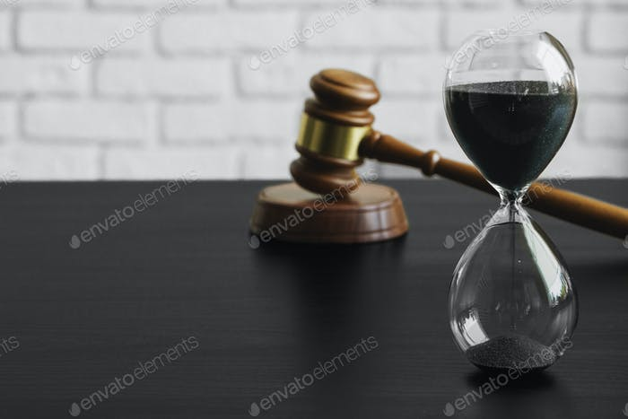 Court concept. Hourglass and judge gavel on table
