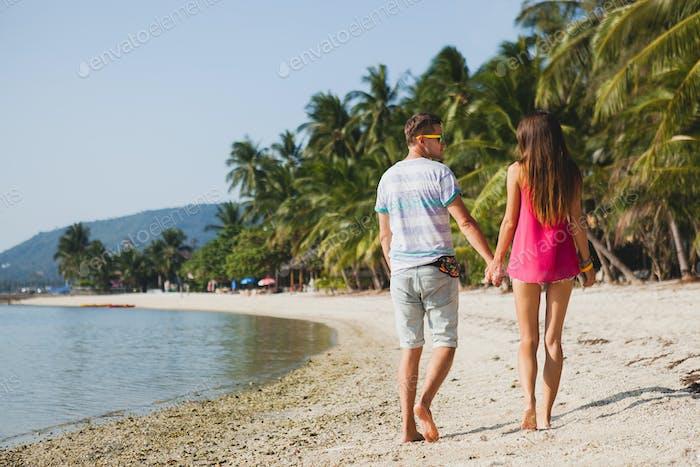 young beautiful couple walking on tropical beach