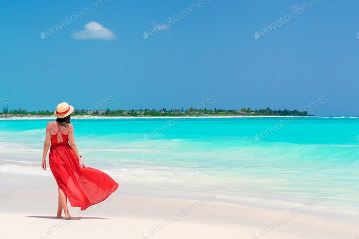 Young girl in beautiful red dress background the sea