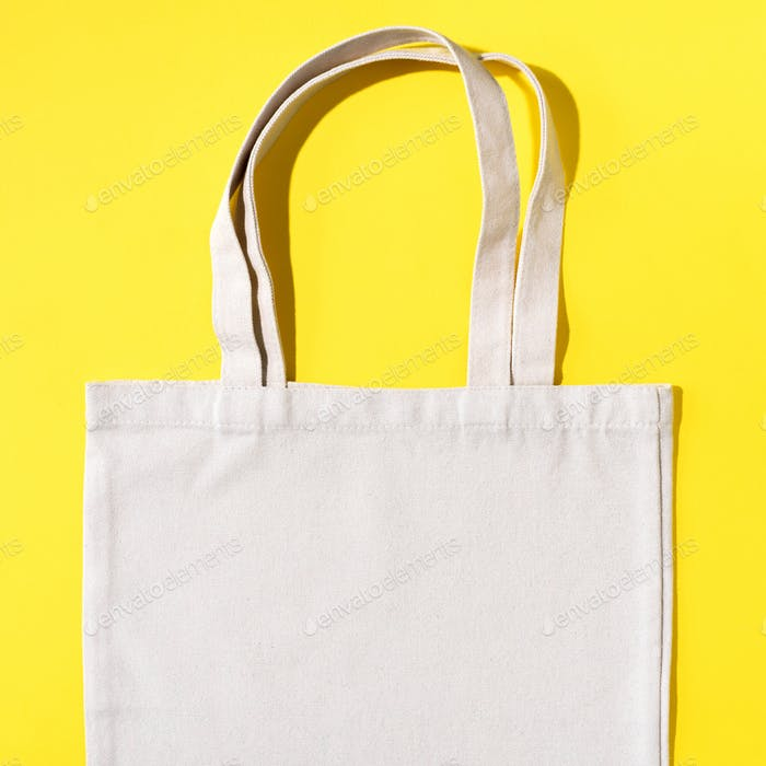 Reusable textile bag on yellow background. Zero waste concept with copy space. Zero waste, plastic