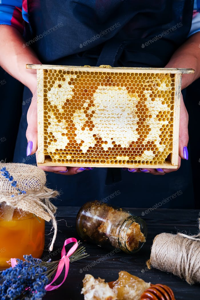 Honey comb with honey. A woman holds honeycomb on a dark background. Healthy Organic Food