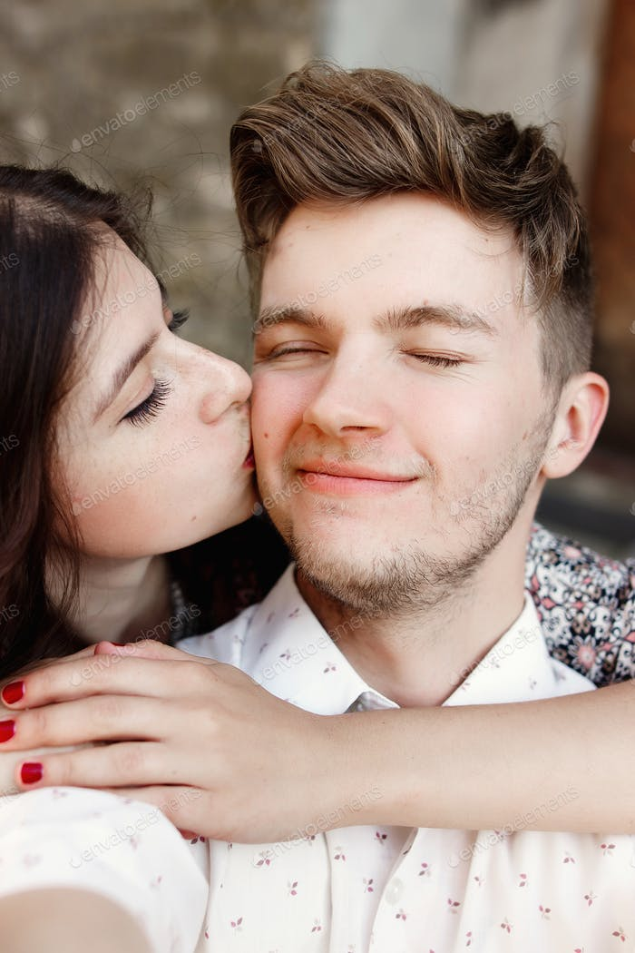 happy stylish couple taking selfie and smiling and kissing