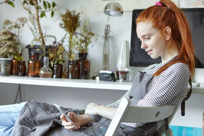 Gorgeous red haired student girl taking part in painting retreat, studying new art techniques, sitti