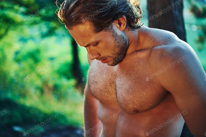 Handsome shirtless man with muscular body type is in the forest at daytime