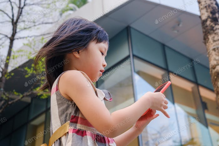 Asian child using cell phone in city