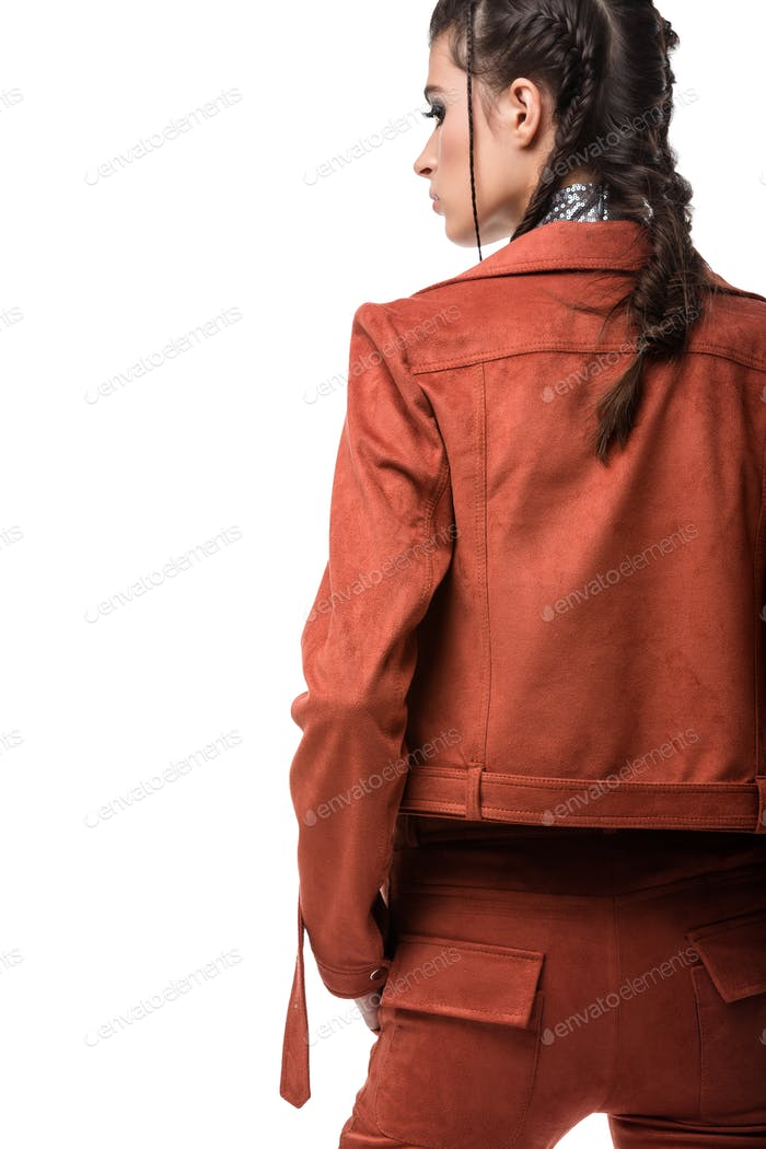 Portrait of young lady standing from back in light brown suede jacket and trousers